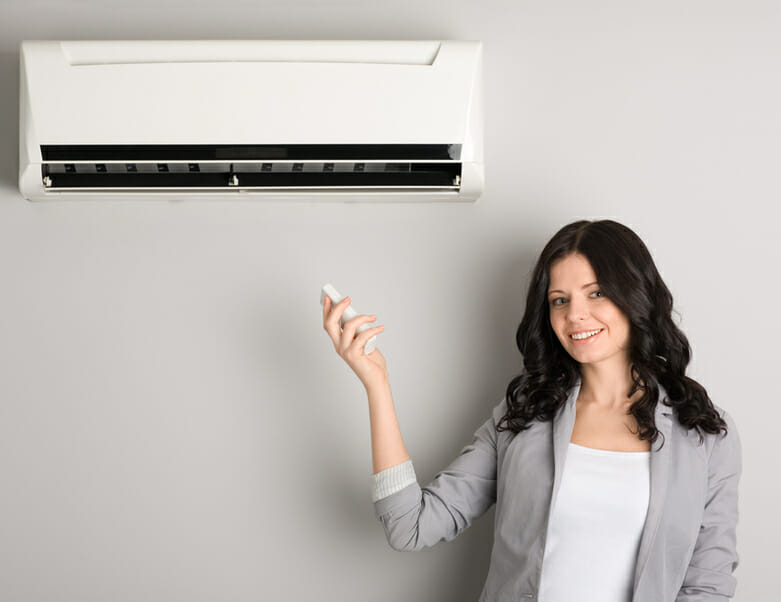 Woman holding remote control of air conditioning