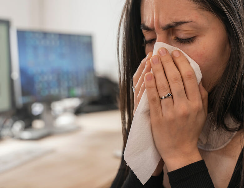 Woman coughing sick in office