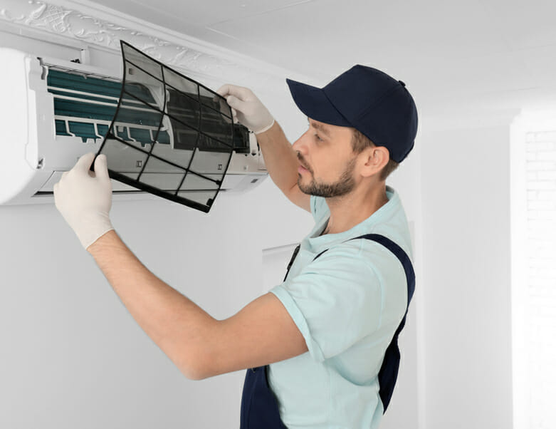Technician cleaning air conditioner indoors