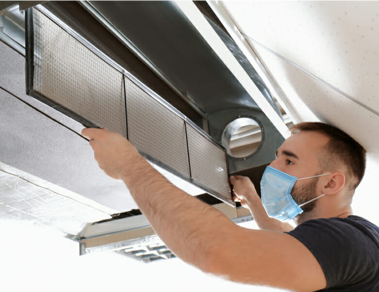 Male technician cleaning an industrial air conditioner