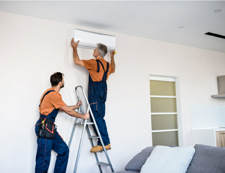 Two workers in uniform installing air conditioning