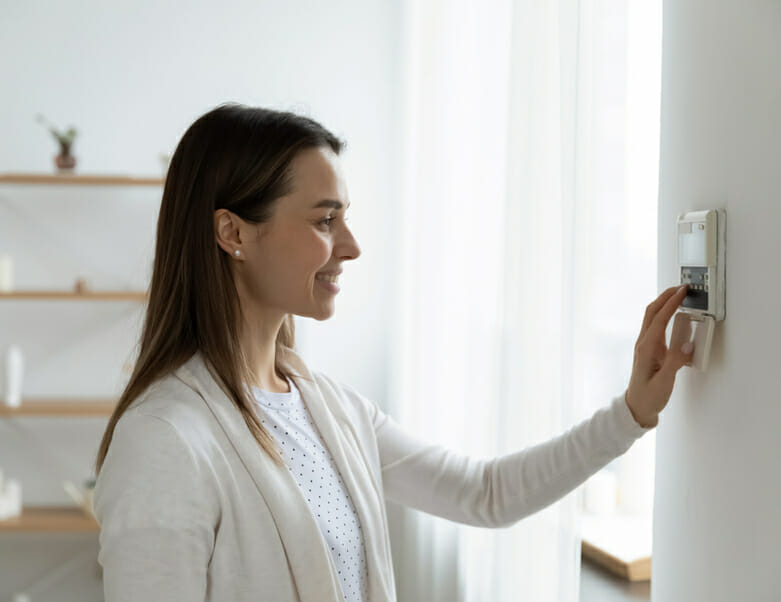 Woman with wall-mounted AC control