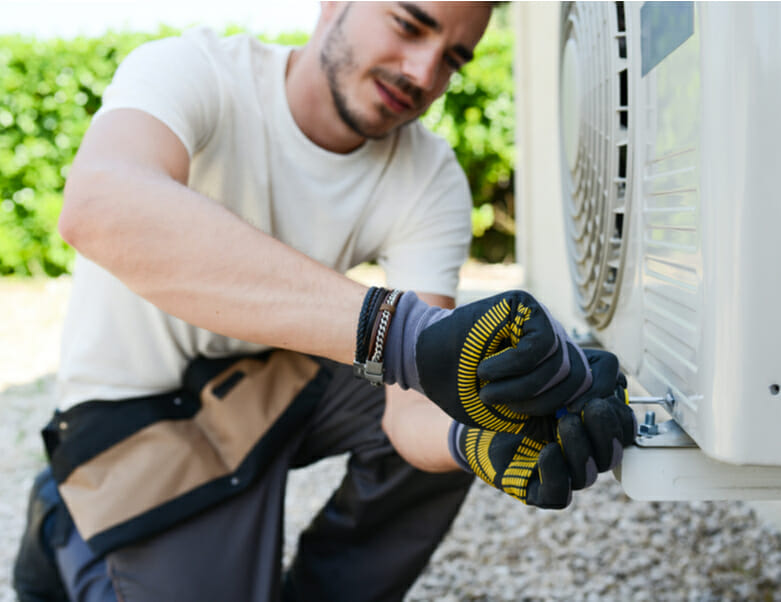 Young man electrician installing air conditioner